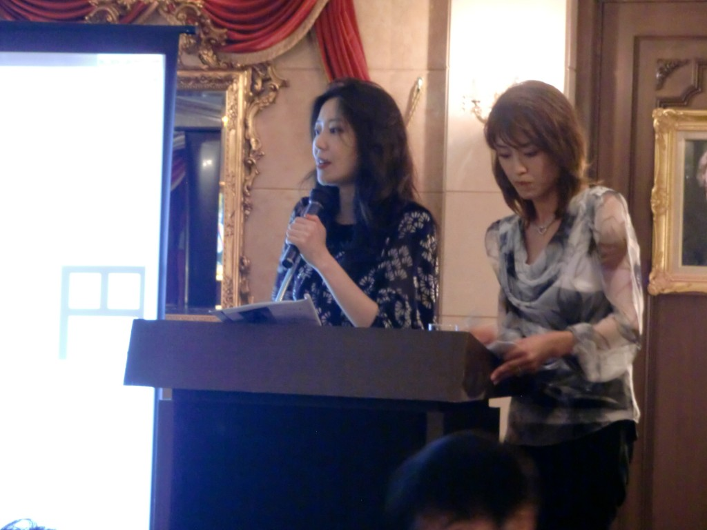 Junko conducting a wine auction.